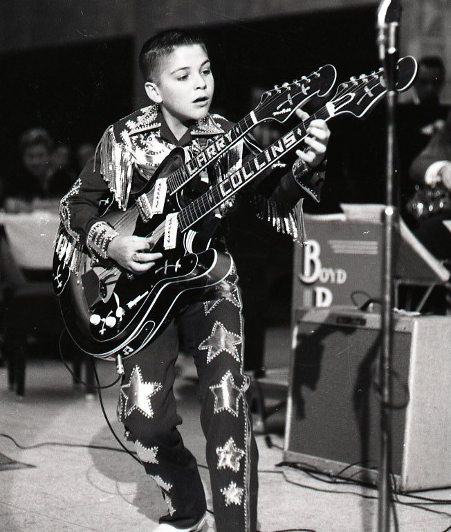 El pequeño Larry Collins con su icónica guitarra de doble mástil.