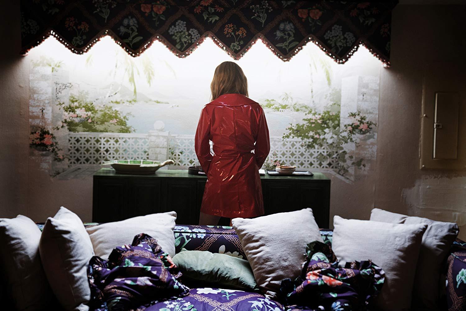 Odessa Young con la icónica gabardina roja.